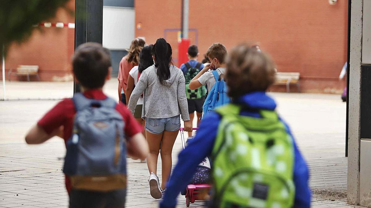 Un grupo de alumnos accede a su centro educativo, en València.