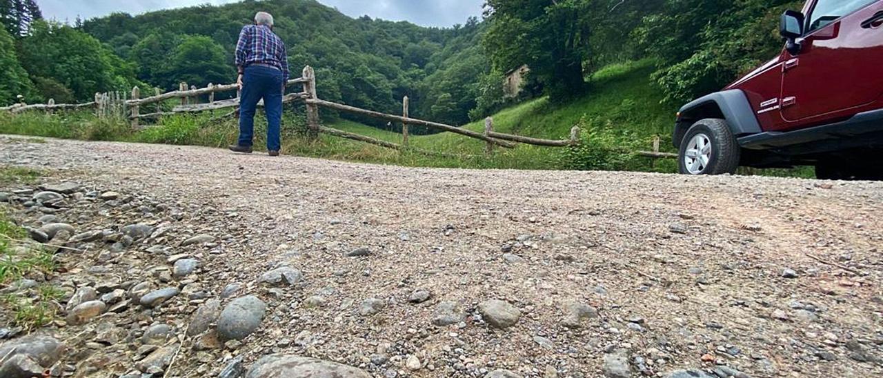 Un vecino pasea por la pista de acceso a la Vía Carisa desde Carabanzo (Lena), con un hundimiento en primer término. | C. M. B.