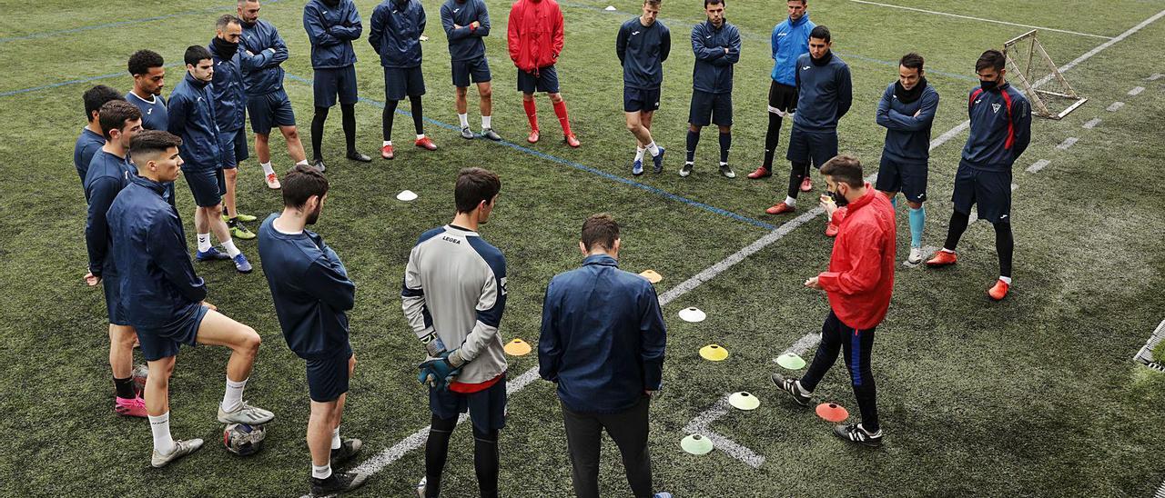 Pablo Busto, tercero por la derecha, da instrucciones a sus jugadores durante el entrenamiento de ayer del Ceares en el campo de Lloreda. | Juan Plaza