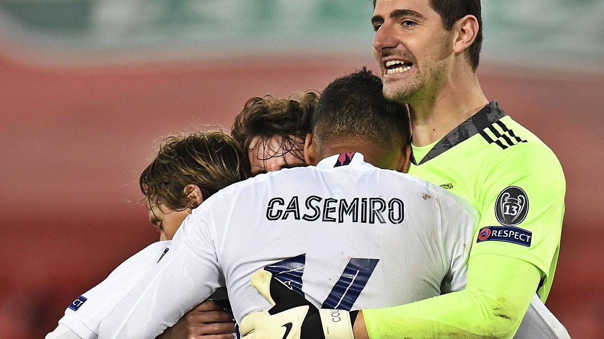 Courtois abraza a sus compañeros del Madrid para celebrar su clasificación para semifinales de la Liga de Campeones.    // PETER POWELL