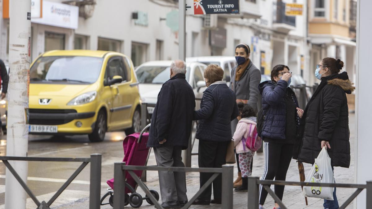 Varios viandantes en la calle de la Reina de Xàtiva, todos protegidos con mascarillas.