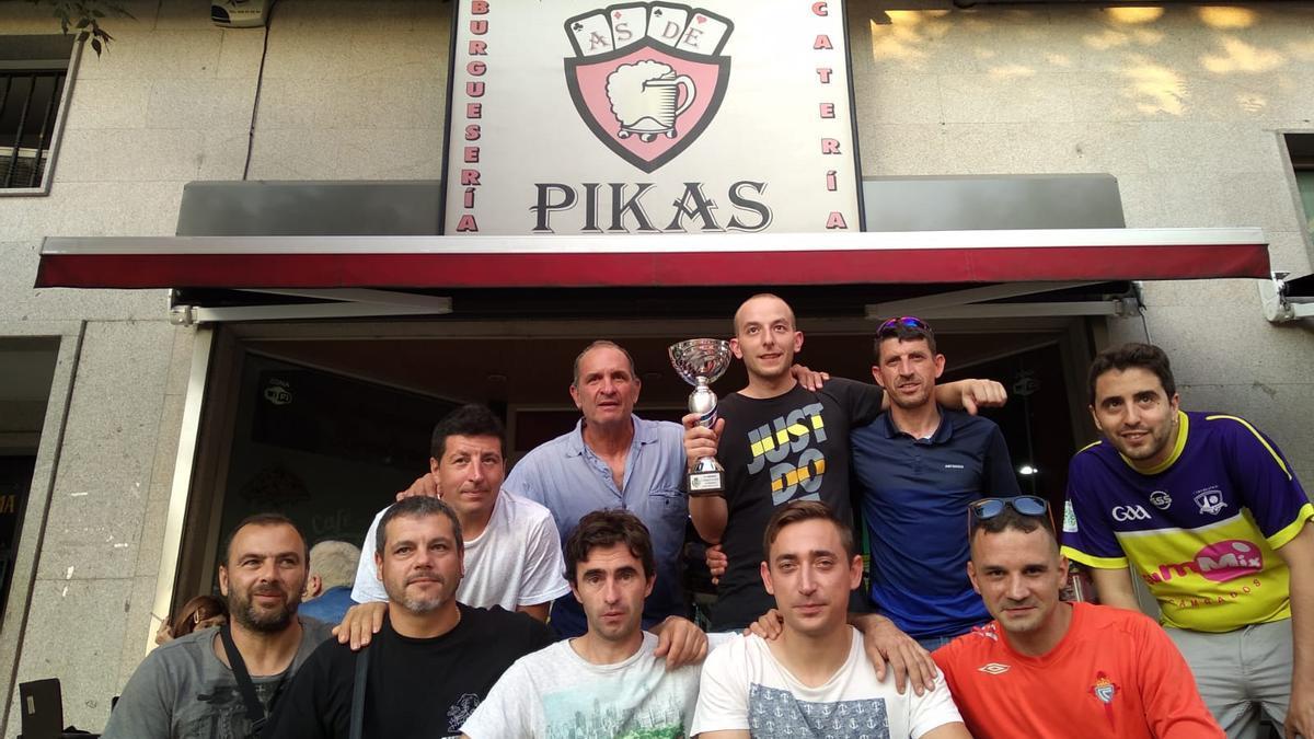 Miguel, el propietario del bar As de Pikas, en la puerta de su local con sus clientes y amigos en una imagen de archivo.
