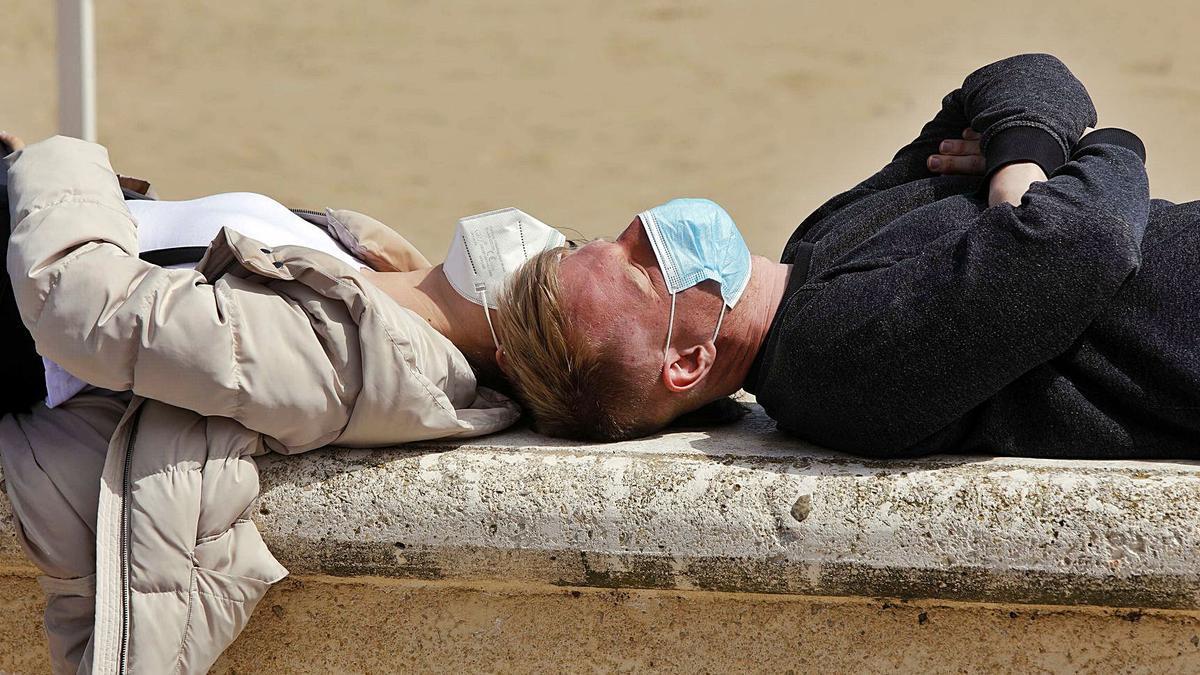Una pareja toma el sol con mascarilla en el paseo marítimo de la playa de la Malva-rosa de València. | M.ÁNGEL MONTESINOS
