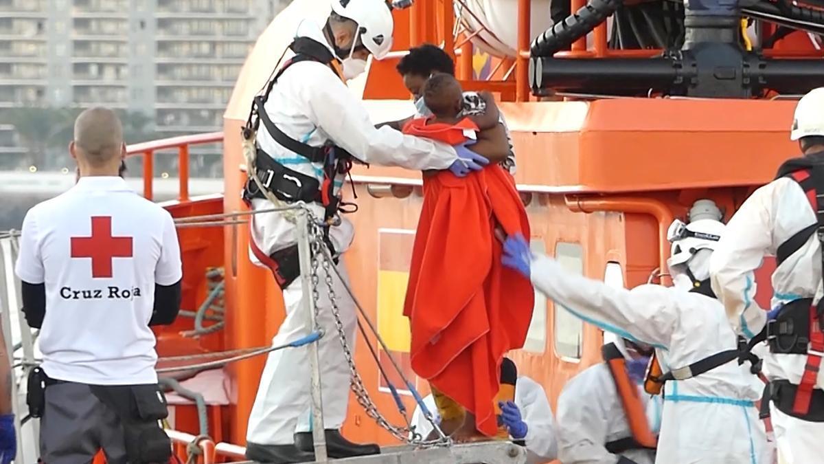 Un miembro de la Cruz Roja ayuda a bajar del barco a una mujer migrante con su niño en el puerto de Arguineguín (Gran Canaria, España) a 17 de marzo de 2021. 79 inmigrantes de origen subsahariano que viajaban a bordo de dos pateras fueron trasla