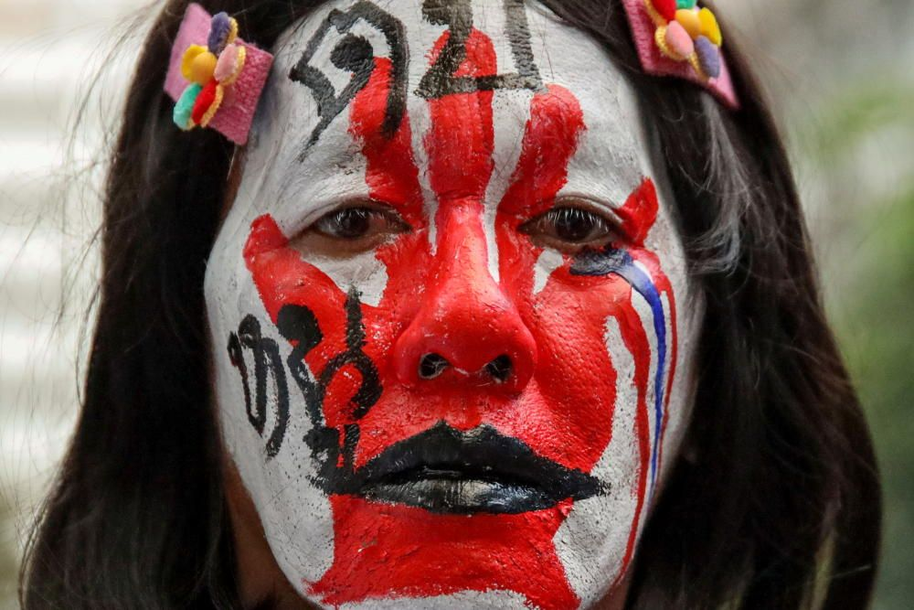A protester with her face painted with words ...