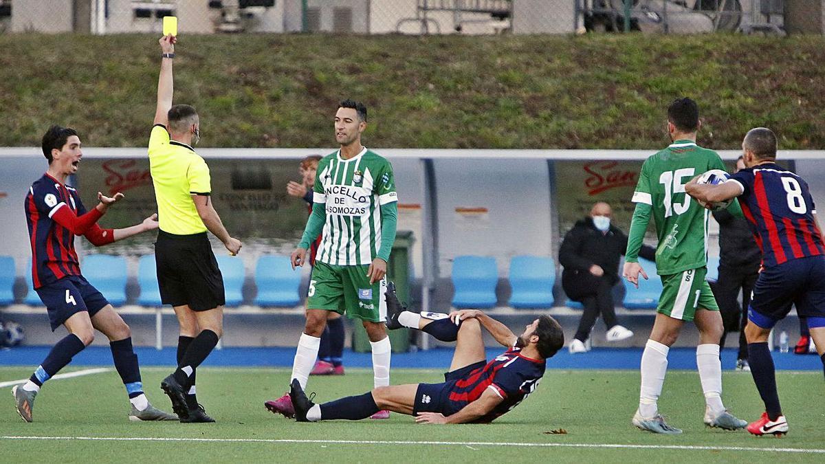 El vigués Miguel Oliveira muestra la tarjeta amarilla a Diego en el Estudiantil-Somozas de ayer. |  // X. ÁLVAREZ