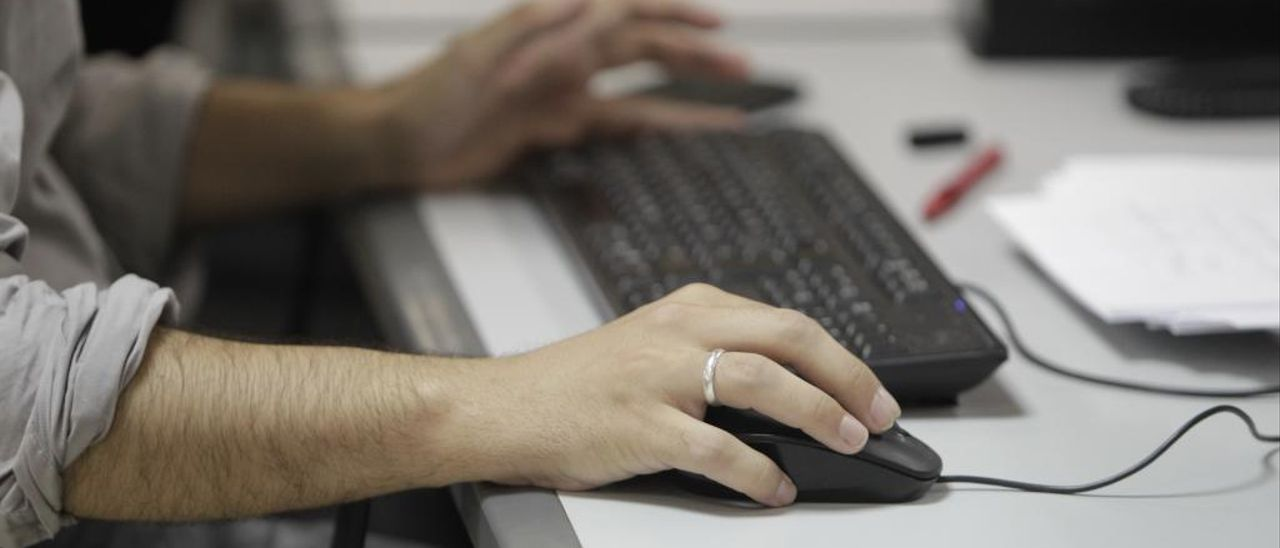 Un trabajador utiliza un ordenador en su puesto de trabajo