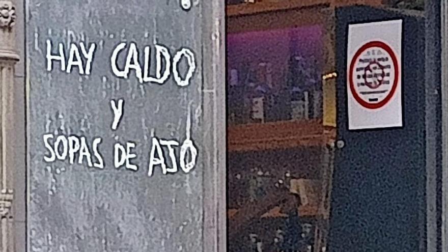 Cartel de caldo y sopa de ajo en pleno verano en un bar de Oviedo