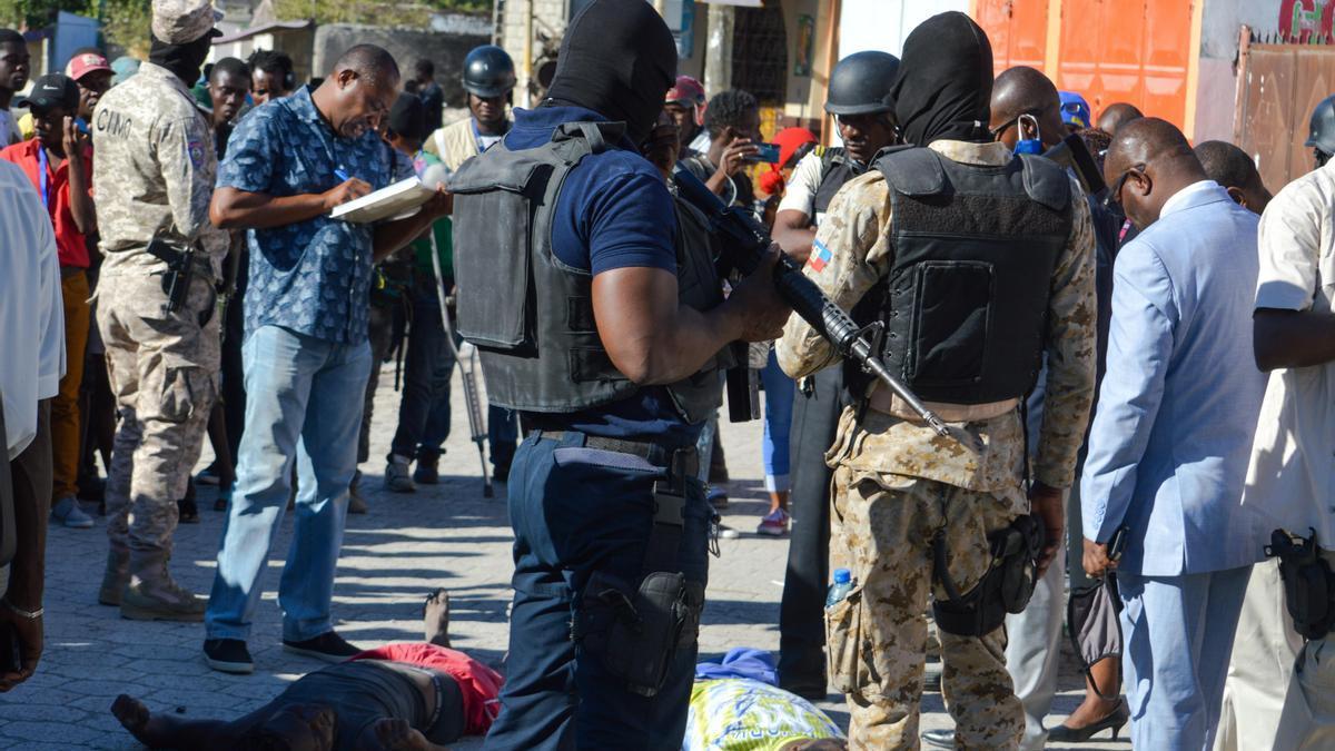 Varias personas y la Policía rodean dos cadáveres tras el motín en una cárcel de Puerto Príncipe.