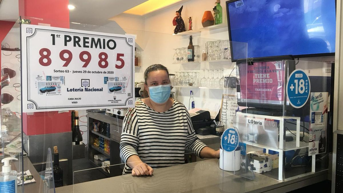La propietaria del Bar Julio con el cartel del número de la Lotería Nacional premiado, en su establecimiento.