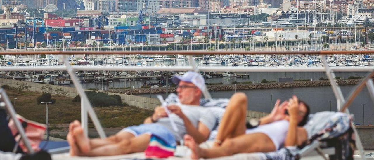 Una pareja se relaja en la cubierta de un crucero atracado en el Puerto de Valencia.