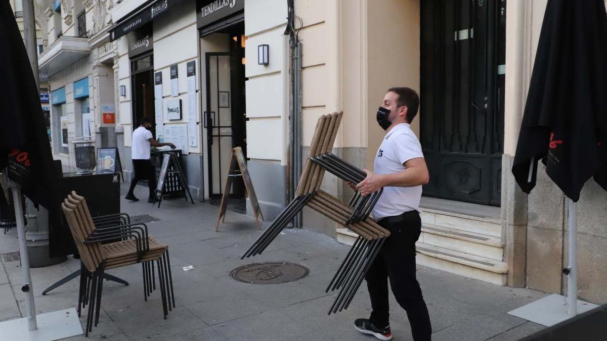Un trabajador coloca los veladores de un establecimiento.