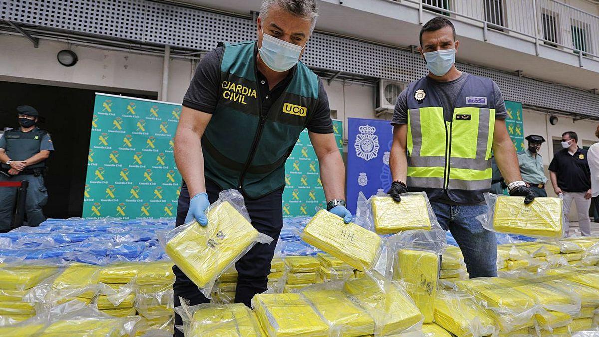 Un guardia civil y un policía nacional posan ante un alijo de varias toneladas en junio de 2020.
