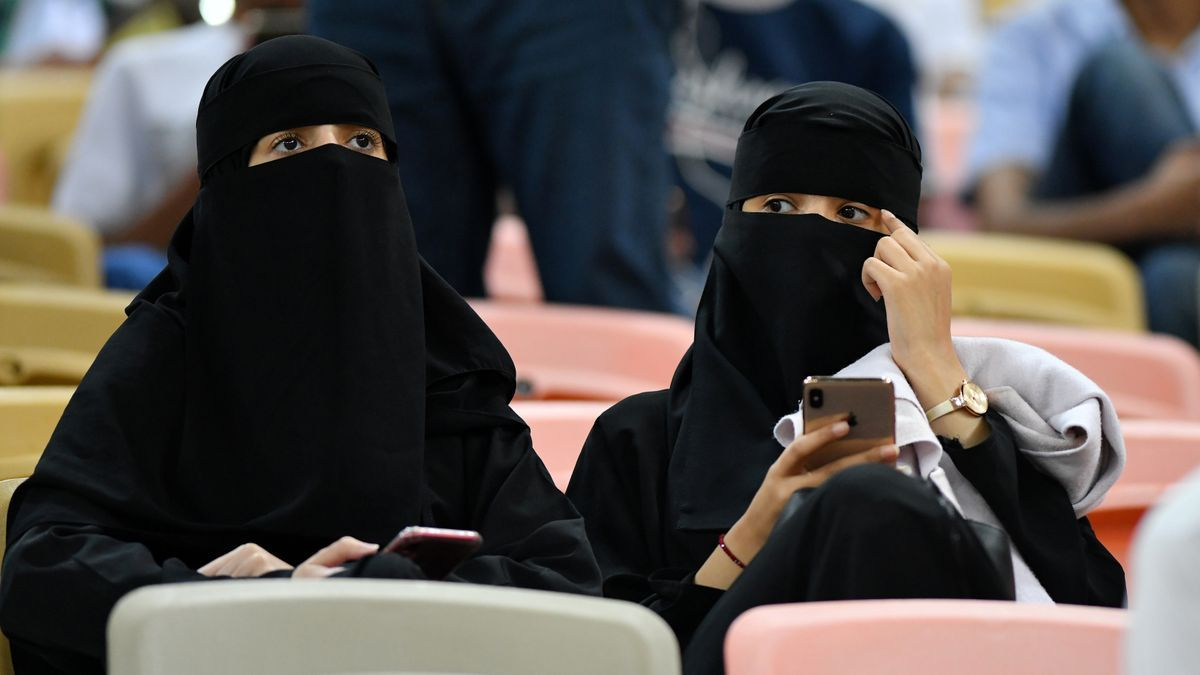 Unas mujeres viendo un partido de fútbol con un burka