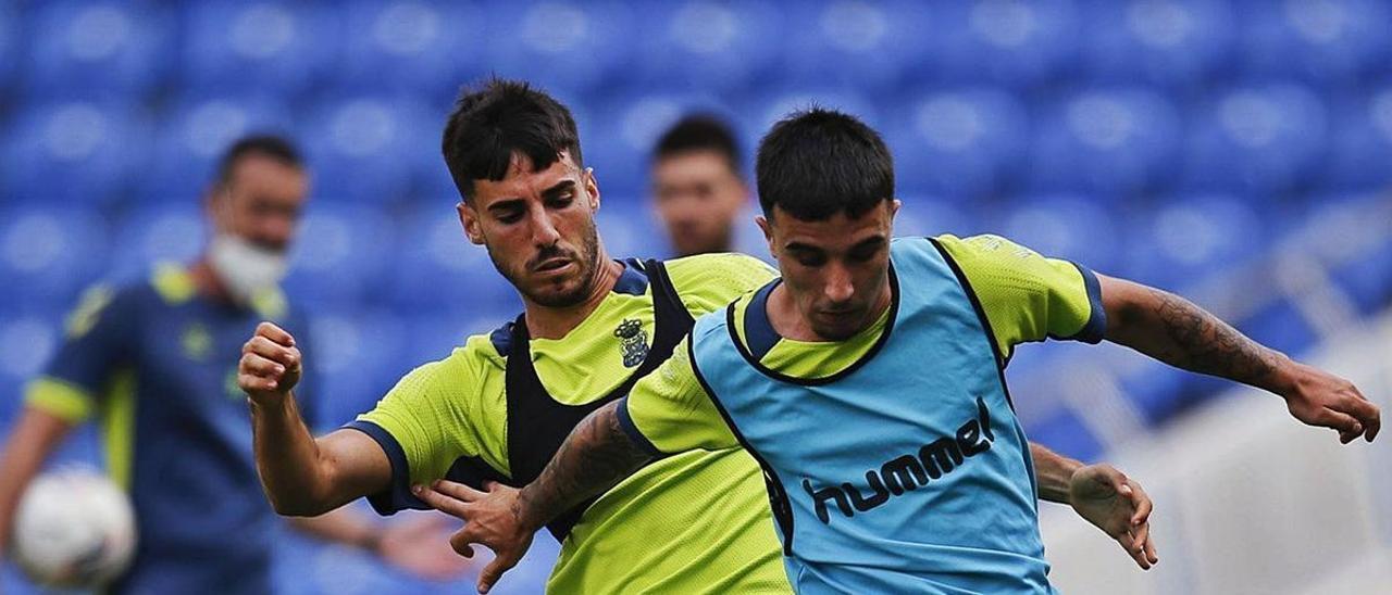 El centrocampista de Ingenio de la UD Fabio González Estupiñán presiona al atacante Rober González, durante la disputa del último 'partidillo' en el Gran Canaria.  | | LP/DLP