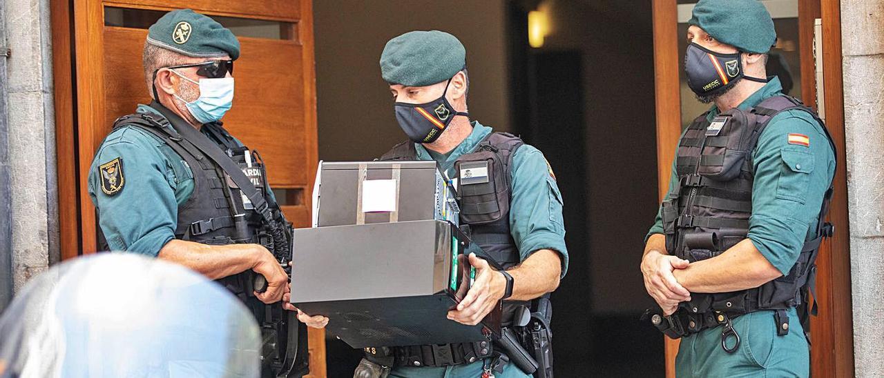 Un guardia traslada documentación intervenida en uno de los registros en Palma.