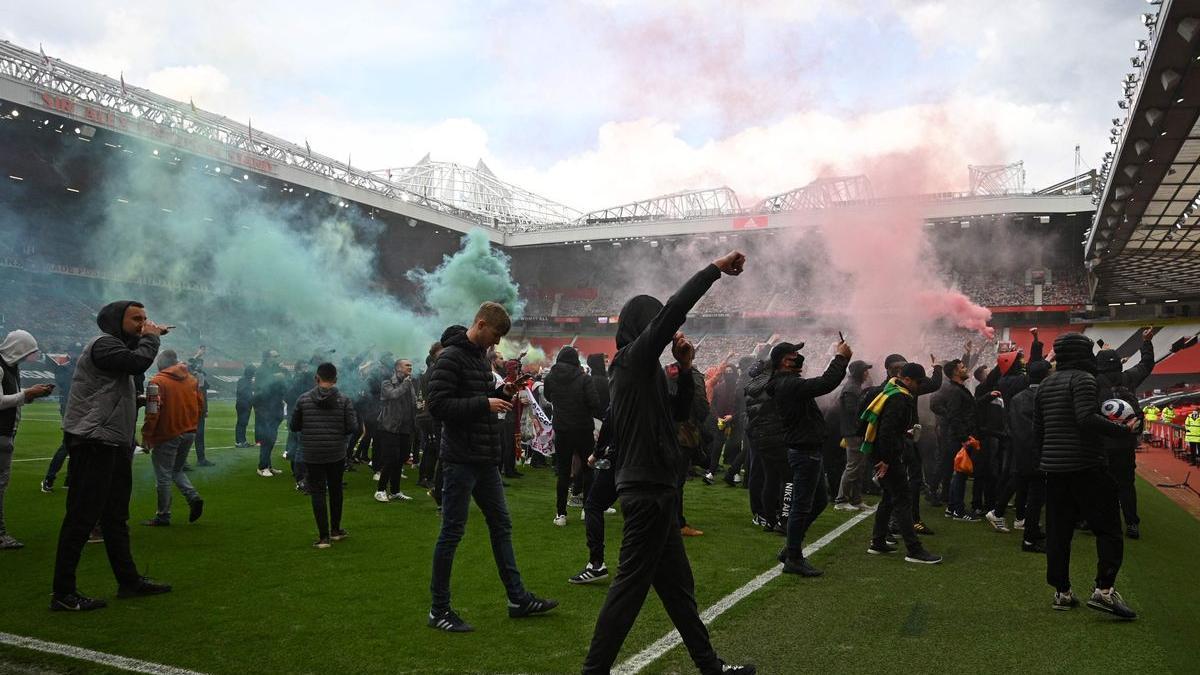 Los seguidores del United, en el césped de Old Trafford. / REUTERS
