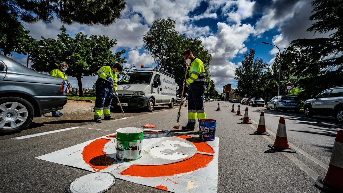 Varios operarios pintan la señalización horizontal en una calle de Badajoz.