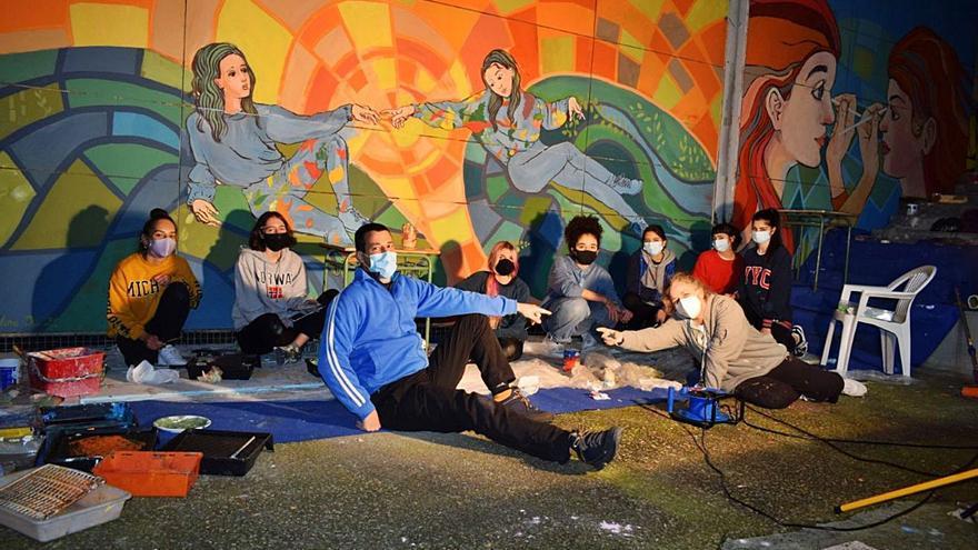 Alumnos del bachillerato de artes pintan de feminismo la plaza de abastos de Moaña