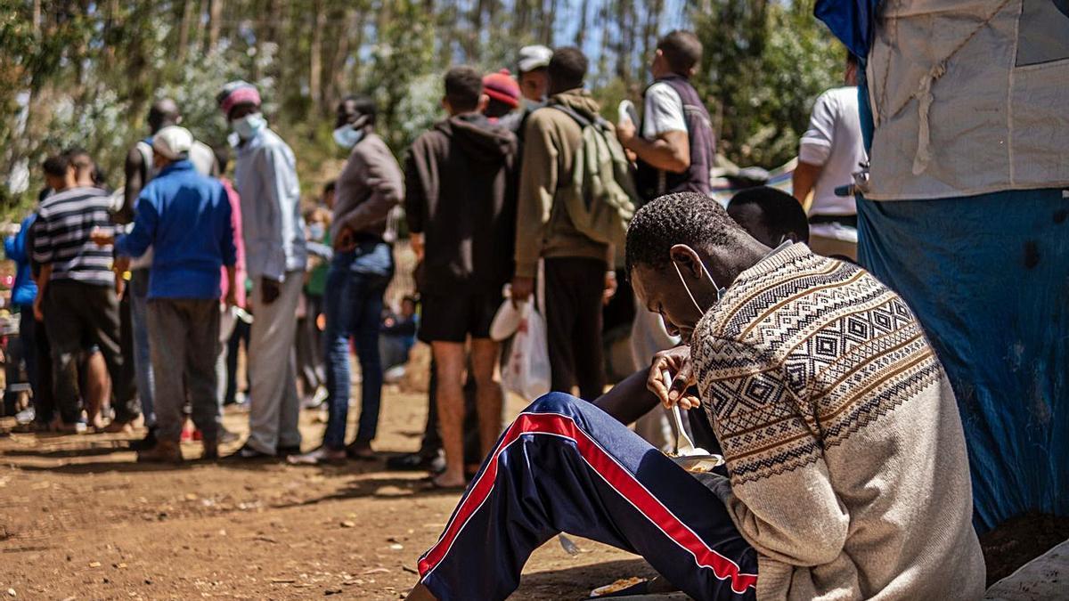 Colas para hacerse con comida de migrantes en el exterior del campamento de Las Raíces durante el Ramadán. | | ANDRÉS GUTIÉRREZ