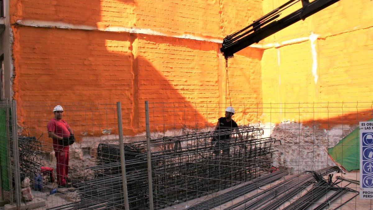 Dos obreros supervisan la descarga de ferralla en la obra.