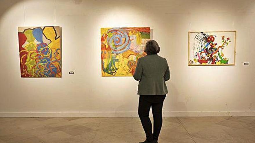 Una mujer observa las obras expuestas en la Alhóndiga.