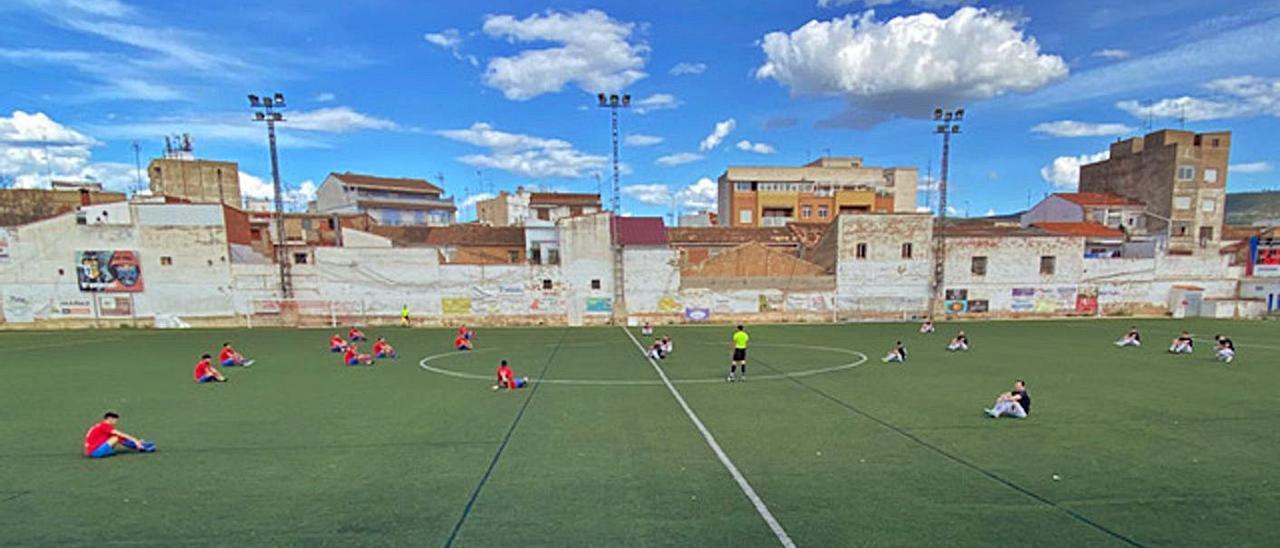 Jugadors asseguts al terra a l'inici de l'últim partit de la UD Canals, aquest cap de setmana   LEVANTE-EMV