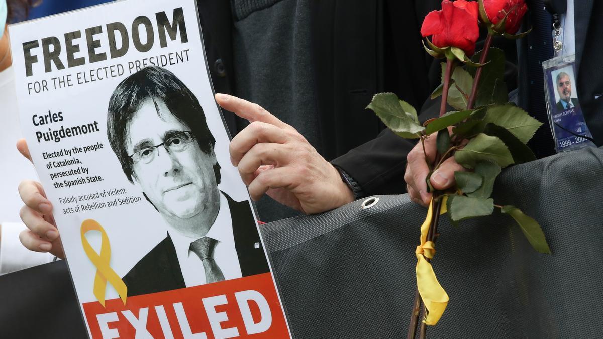 Un manifestante sostiene un cartel de Puigdemont en una concentración en Barcelona.