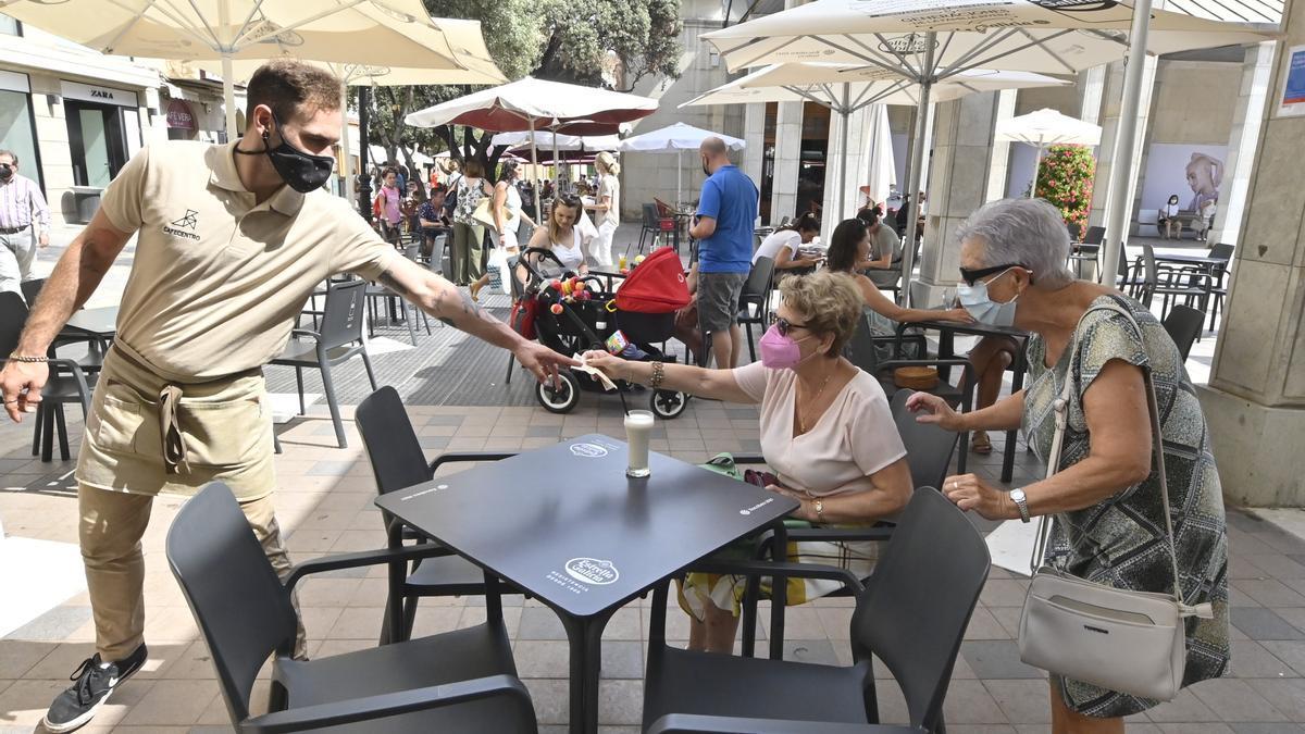 Un camarero mientras atendía este martes a dos mujeres en un establecimiento hostelero ubicado en la conocida plaza Santa Clara de la capital de la Plana.