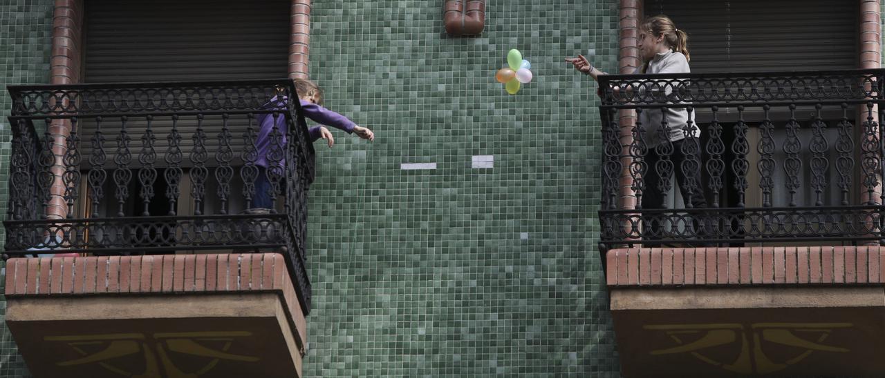 Dos niñas en los balcones de sus casas durante el confinamiento