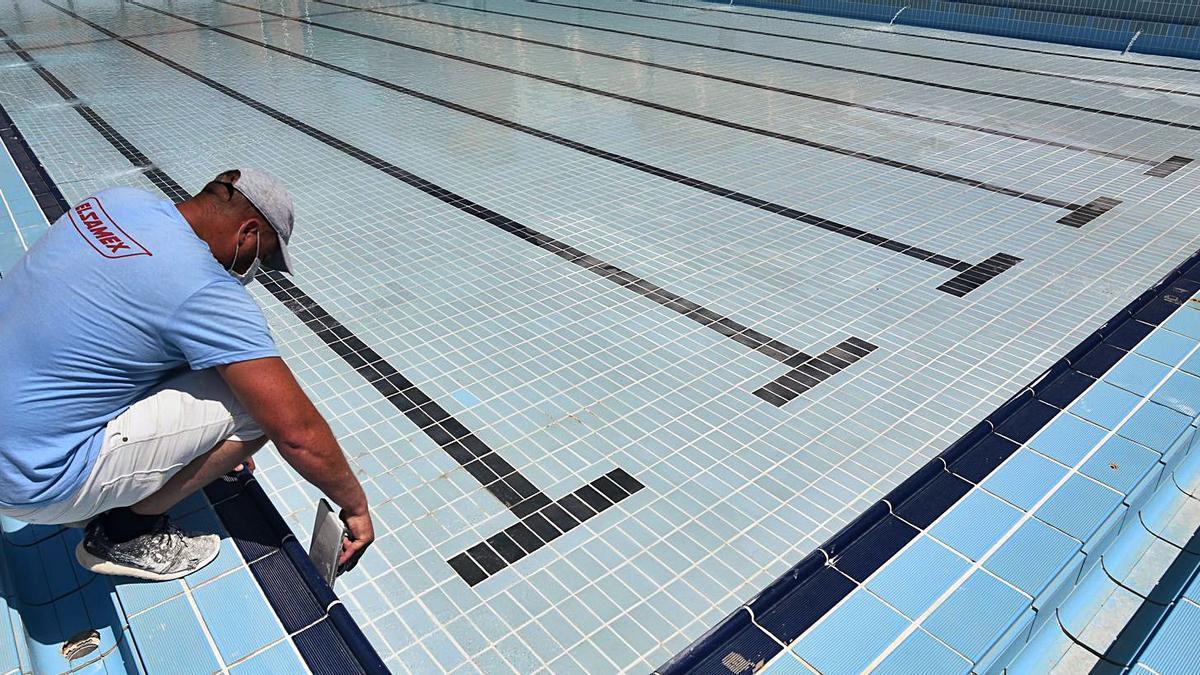 Un empleado comprueba el estado del agua, ayer en una de las piscinas de Murcia Parque. | ISRAEL SÁNCHEZ