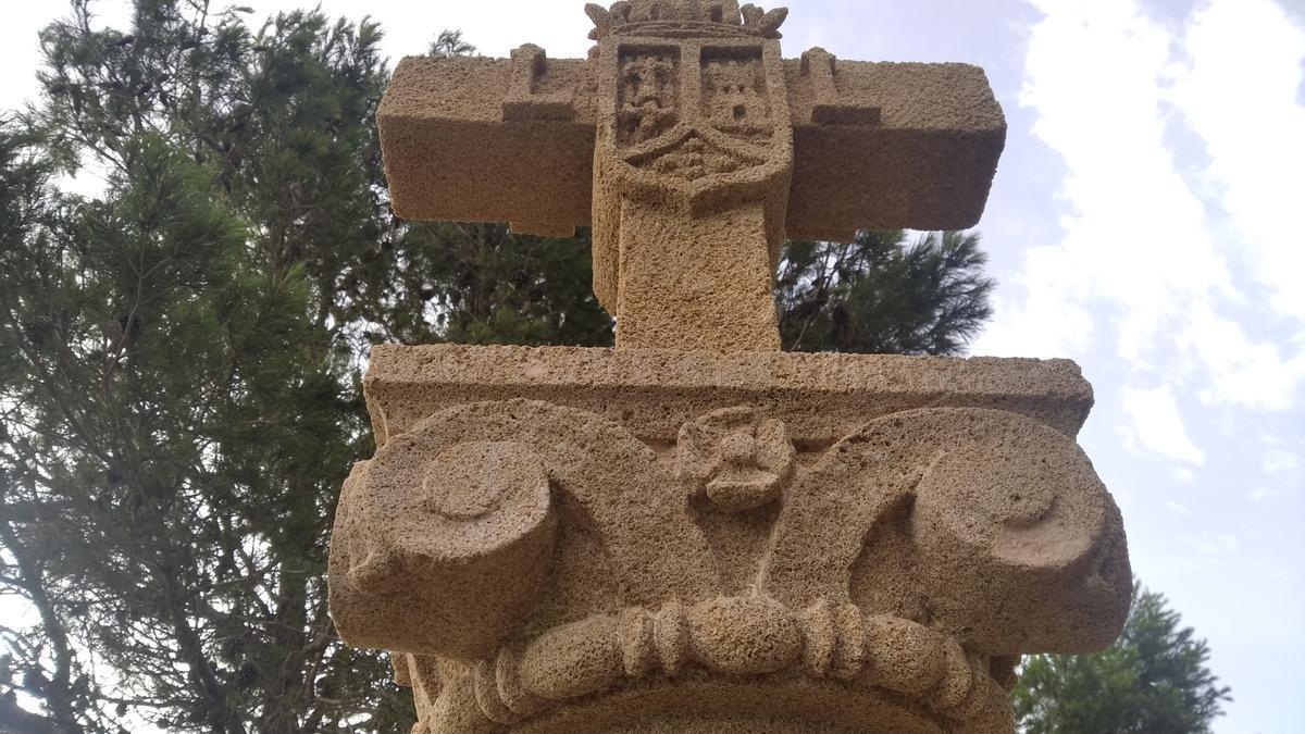 La cruz con el escudo labrado y el capitel corintio