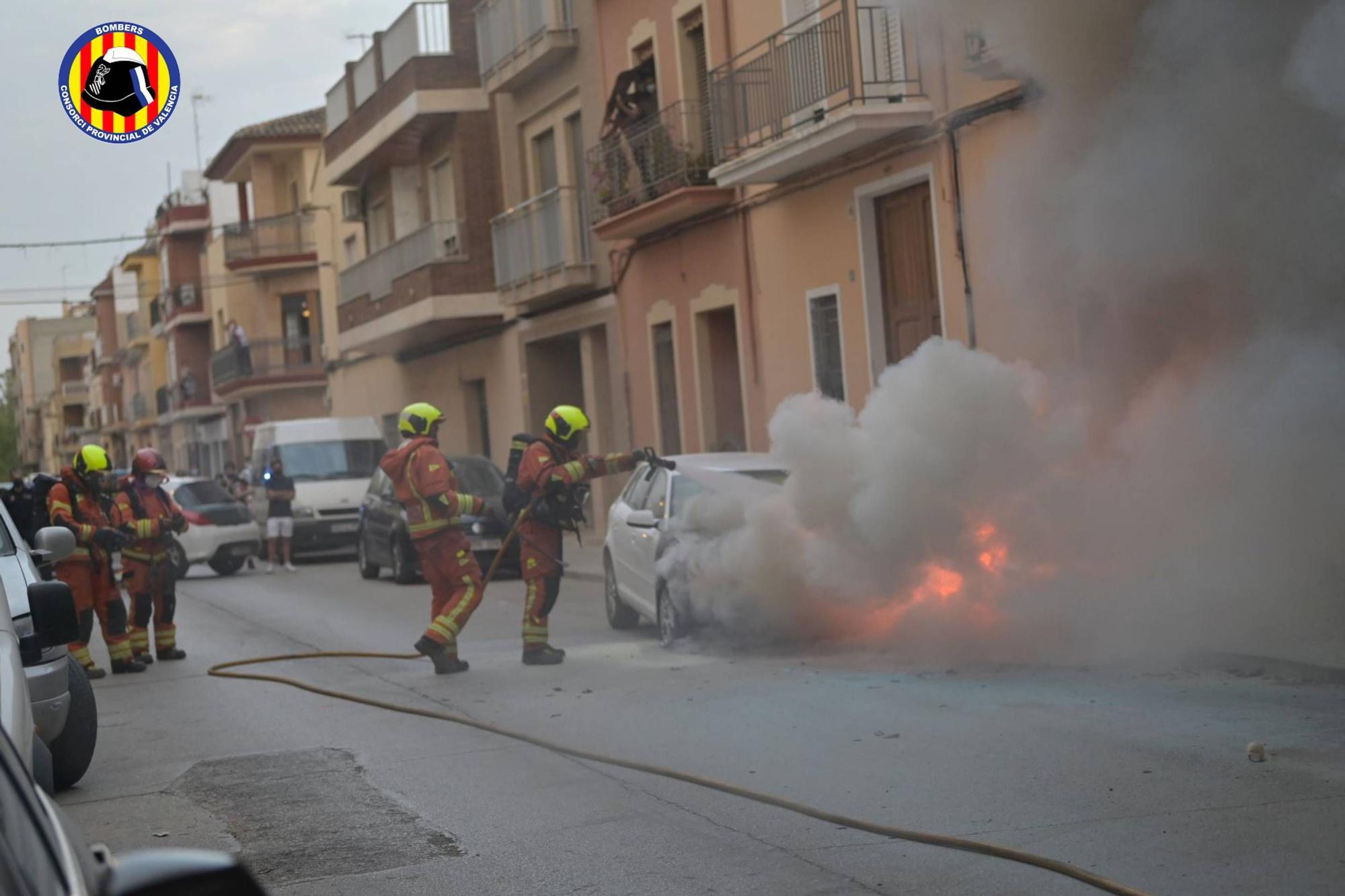 Los bomberos apagan un vehículo incendiado en plena calle en Carlet