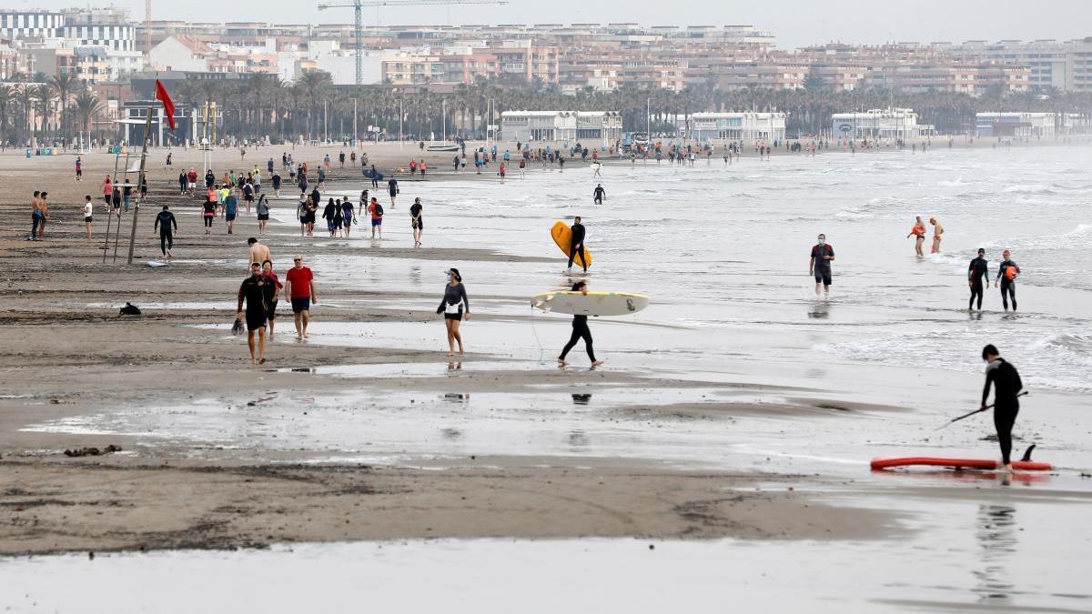 Bañistas, surferos y caminantes en la playa de Las Arenas.
