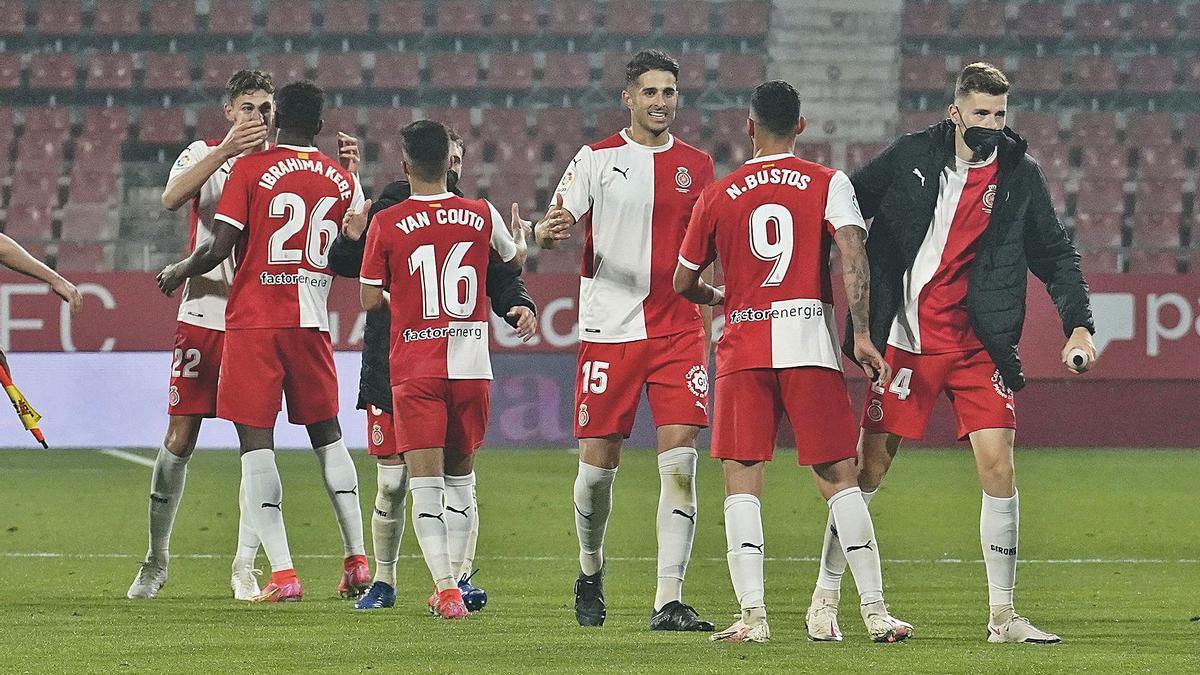 Diversos jugadors del Girona felicitant-se pel triomf, al final del partit, amb Juanpe, el protagonista, al centre.   MARC MARTÍ