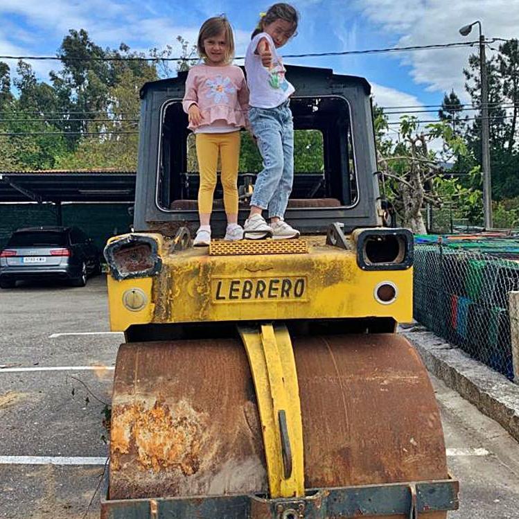 Dos niñas sobre la apisonadora que las familias restauran para el patio.