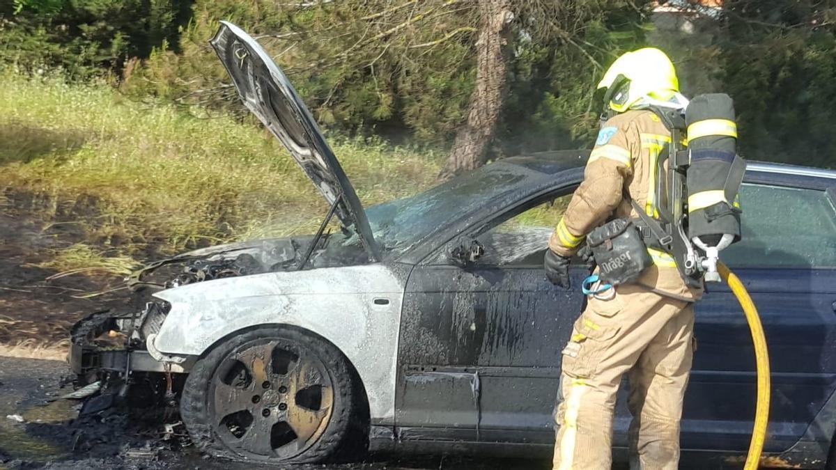 Un bombero sofoca el incendio declarado en un vehículo este viernes en la avenida del Ferrocarril.