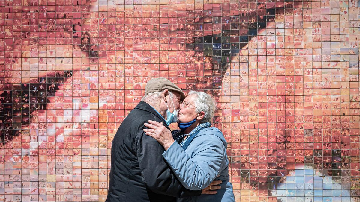 Dos mayores se besan frente a un mural en Barcelona.