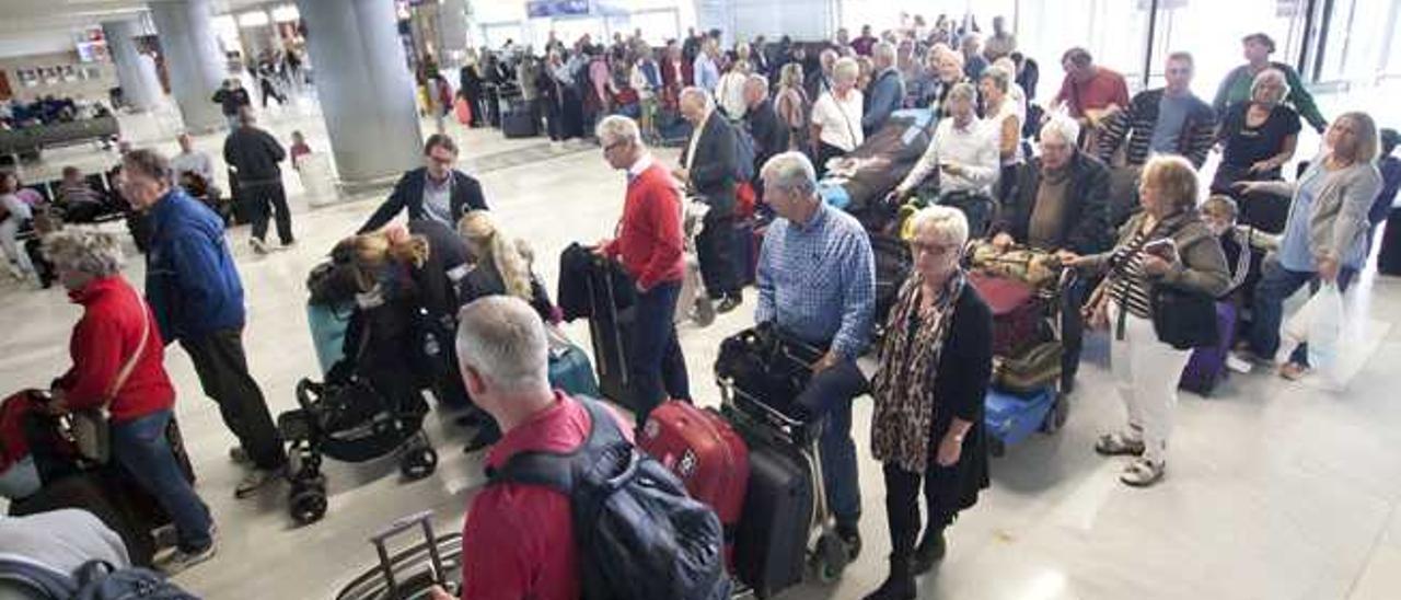 Imagen de turistas haciendo cola para facturar en el aeropuerto majorero.
