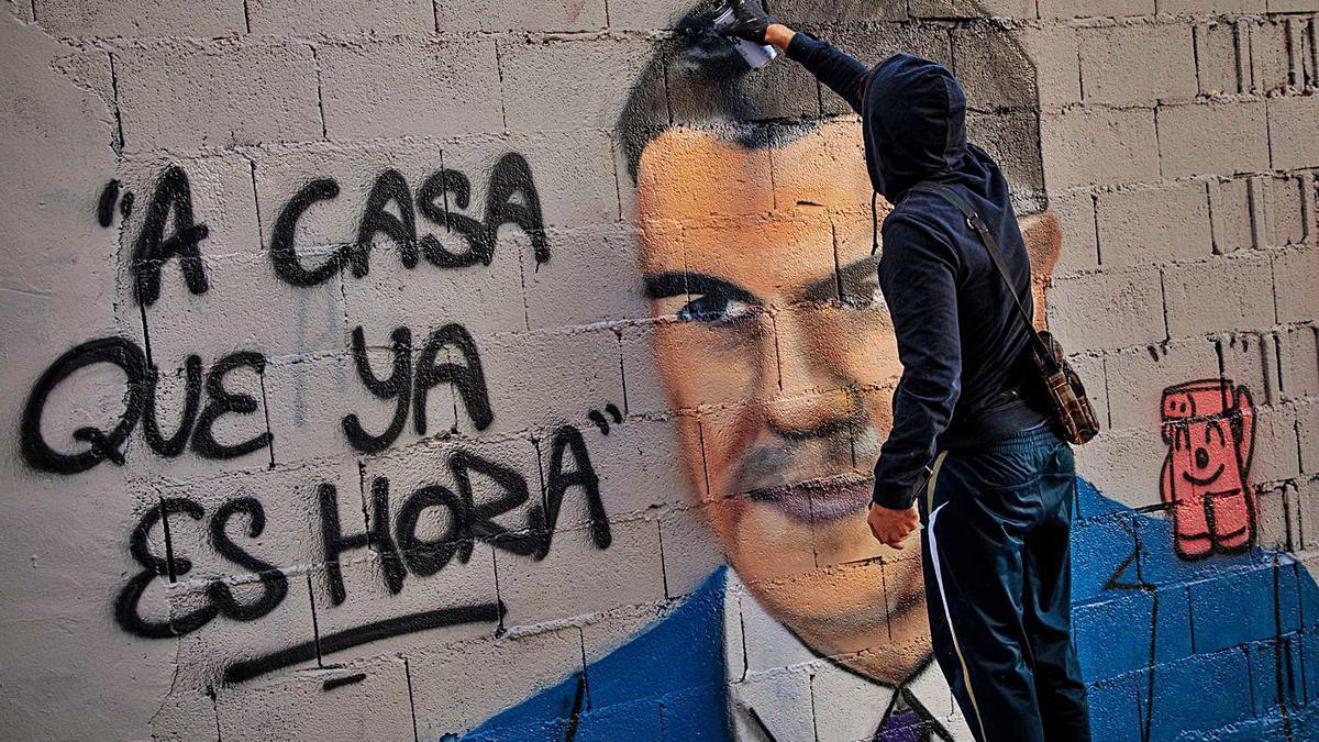 El artista J. Warx pinta en Valencia un grafiti que ironiza sobre un tuit que Sánchez escribió en 2012.