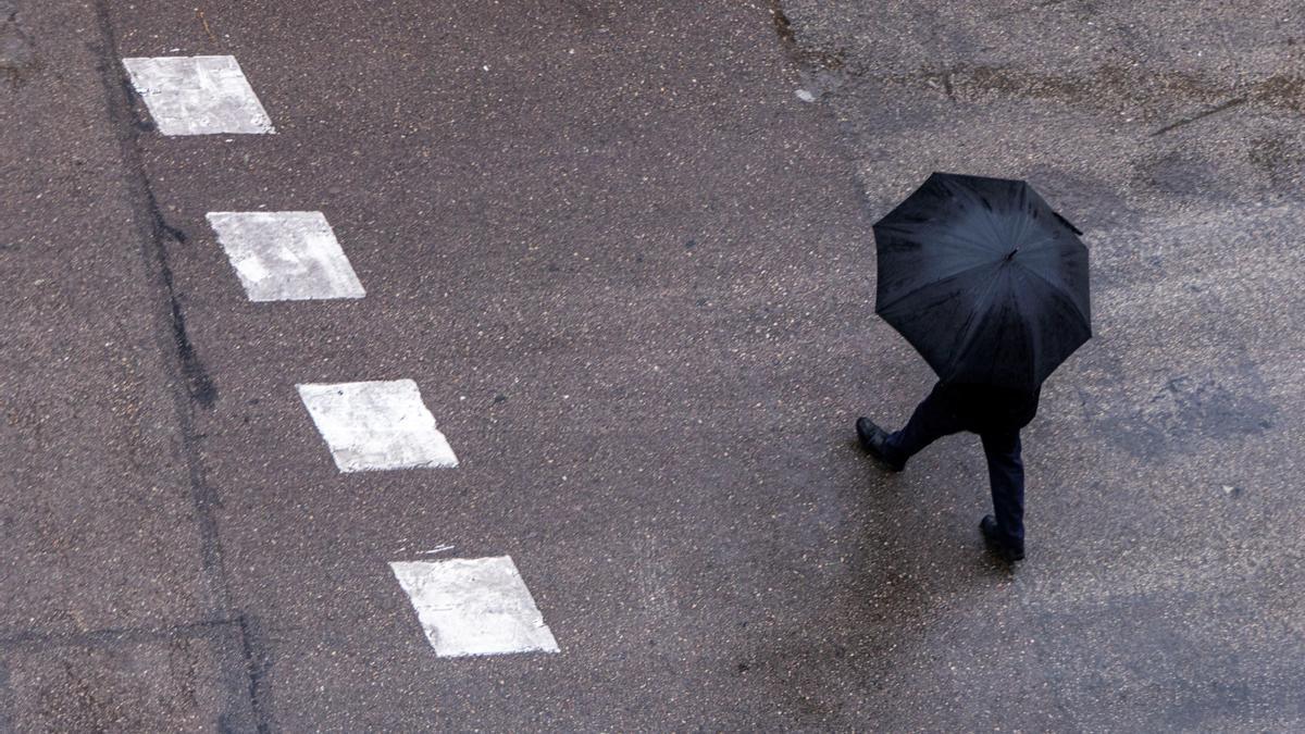 Un hombre cruza un paso de cebra bajo un paraguas.