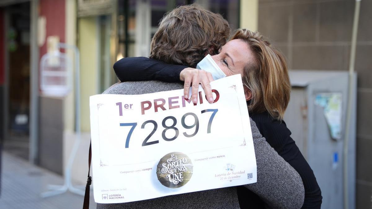 Dos mujeres se abrazan en la administración de lotería de Punta Umbría en la que se ha repartido parte del Gordo.