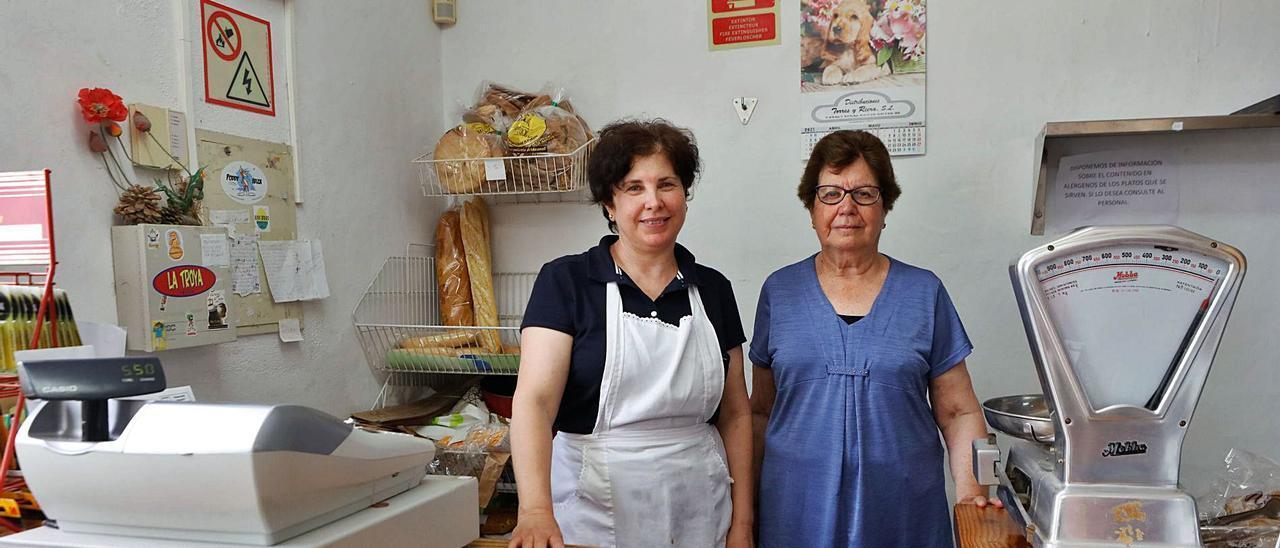 Cati Roig, actual trabajadora de la tienda (con delantal) y su tía, Catalina Marí, con la vieja báscula de su abuela.