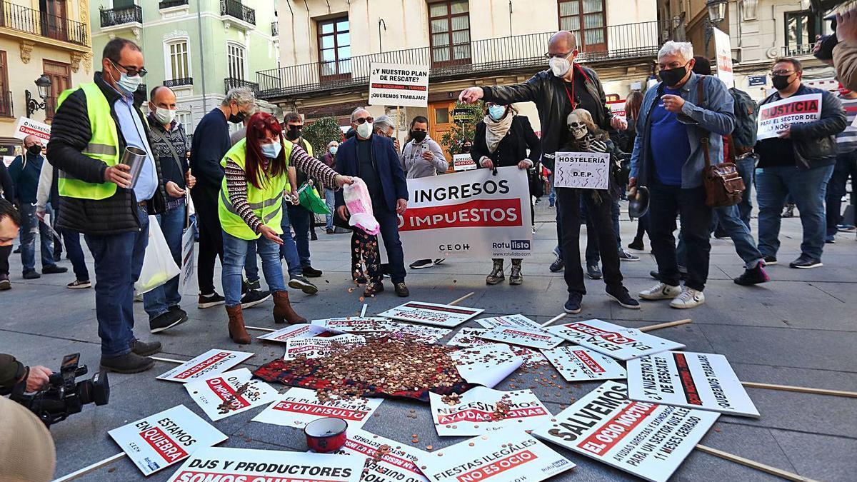 Manifestantes lanzan céntimos a las puertas de la Generalitat en símbolo de protesta. A la derecha, Salvador Navarro y Eva Blasco, líderes de la CEV, en la concentración. | F. CALABUIG