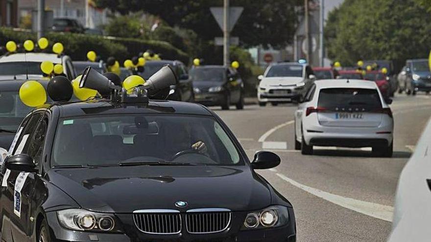 Los interinos reclaman estabilidad laboral con una caravana de cien coches