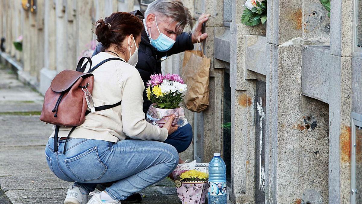 Dos personas, ayer, dejando flores a un ser querido en el cementerio vigués de Teis. |   // MARTA G. BREA