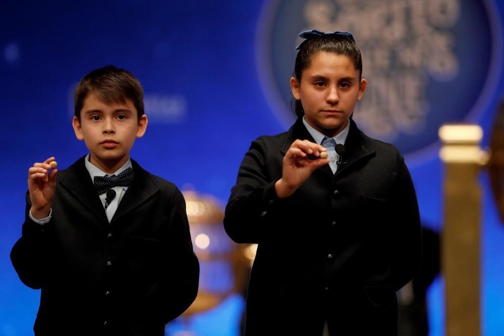 Los niños del colegio de San Ildefonso Nerea Pareja y Luis Alcides muestran las bolas con el número 41.710, que ha sido agraciado con el primero de los dos cuartos premios,