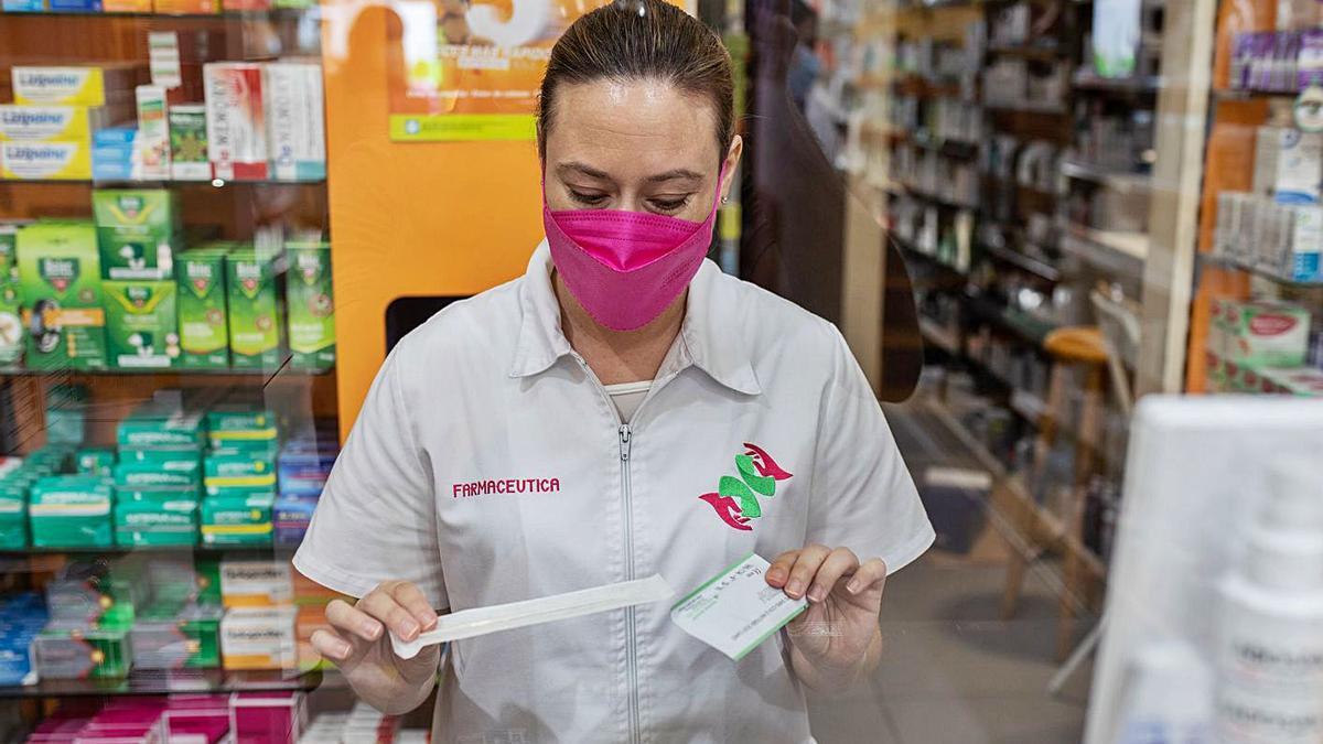 La regente de una farmacia sostiene el hisopo y la placa incluidos en el kit de autotest.   Emilio Fraile