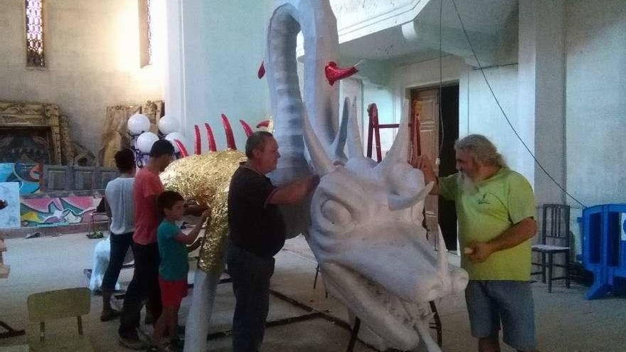 Integrantes de la asociación de carrocistas tradicionales decoran la figura central del montaje.