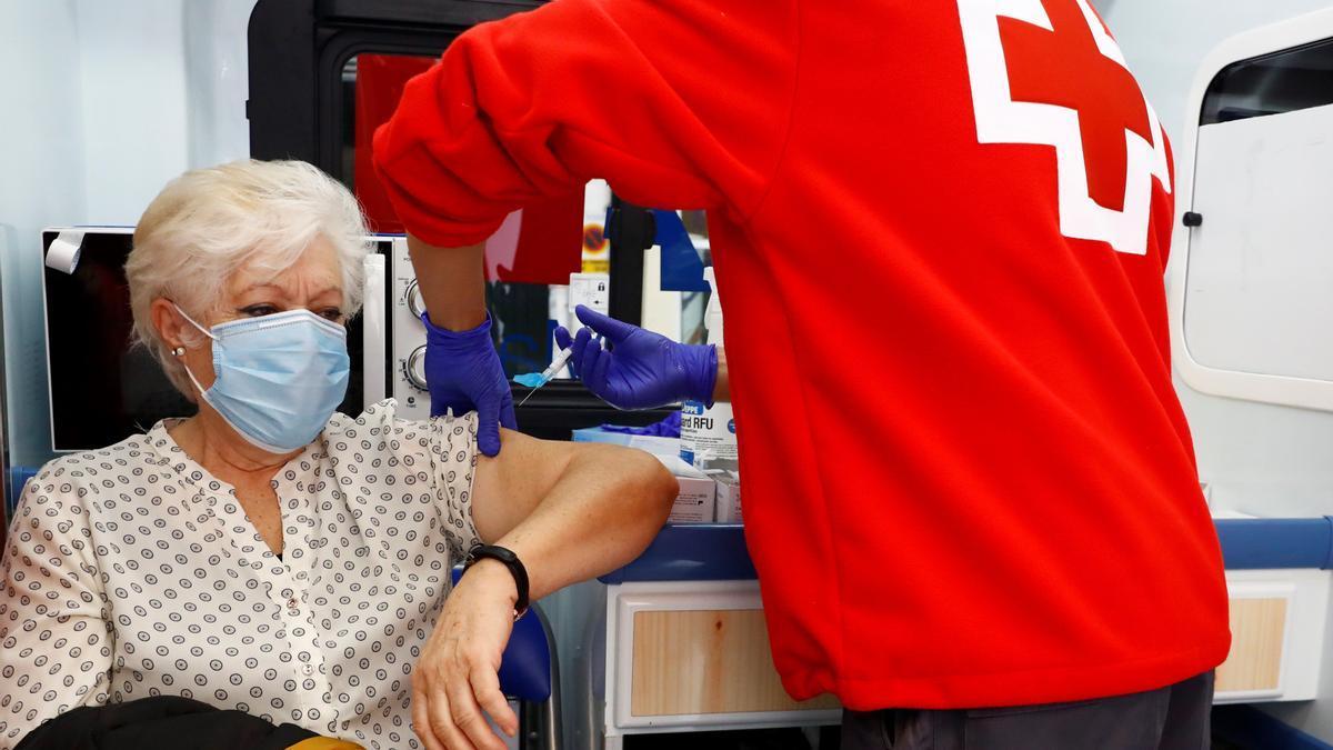 Un miembro de la Cruz Roja vacuna de la gripe a una mujer.